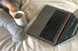 laptop and coffee on bed